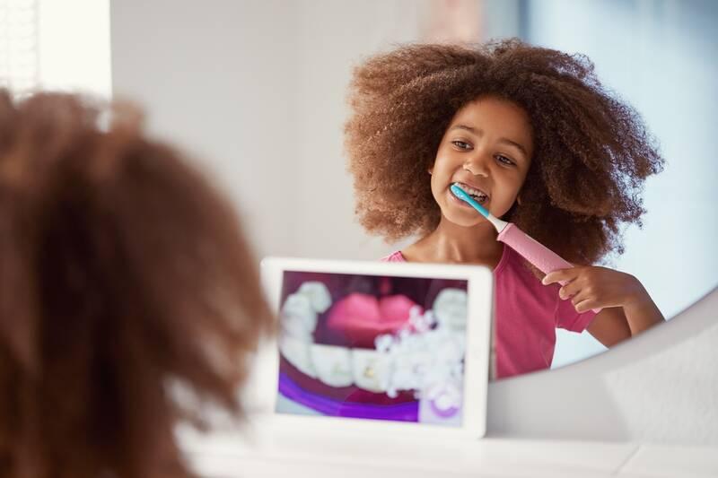 Dievča si čistí zuby elektrickou zubnou kefkou pre deti