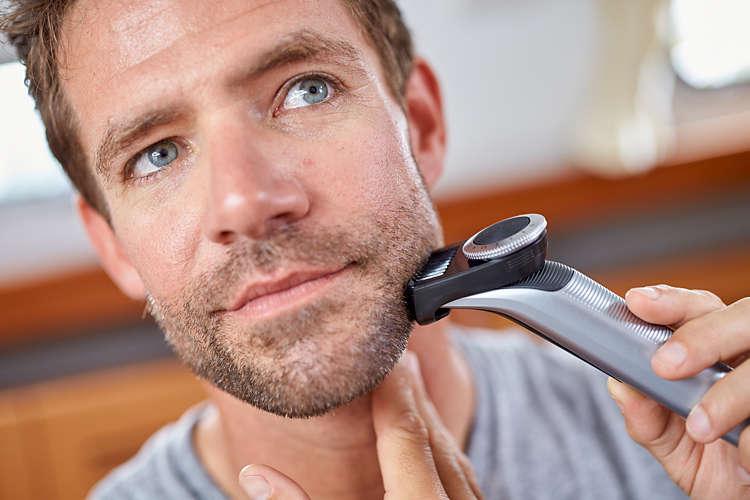 Muž si upravuje bradu pomocou zastrihávača fúzov